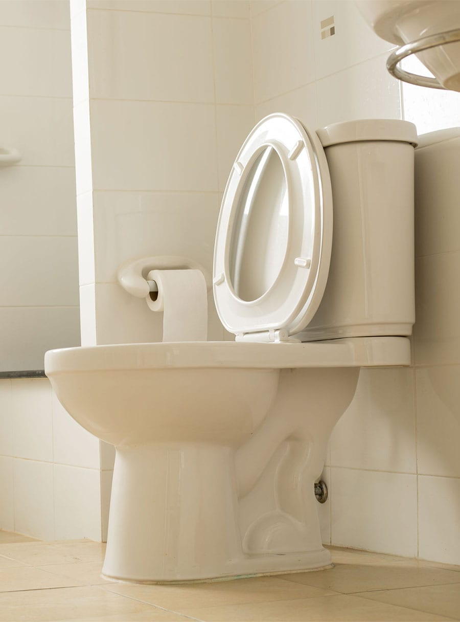 White toilet in a bathroom after sewage damage cleanup